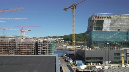 neúplný : OSLO, NORWAY - JUNE 30, 2018: Construction of a new modern elite residential areas. Building site with cranes and containers in Bjorvika in Oslo, next to the Opera House.