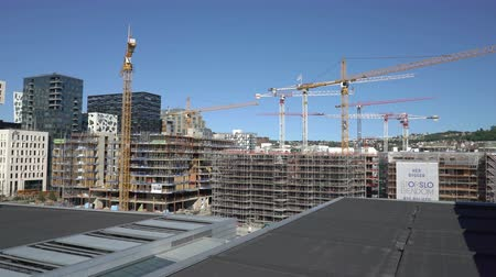 dach : OSLO, NORWAY - JUNE 30, 2018: Construction of a new modern elite residential areas. Building site with cranes and containers in Bjorvika in Oslo, next to the Opera House.