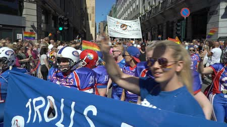 af : OSLO, NORWAY - JUNE 30, 2018: The womens American football team is on the equality March. The Pride Parade, the highlight of Oslo Pride Week, is a huge, vibrant parade filling the city streets. Slow motion