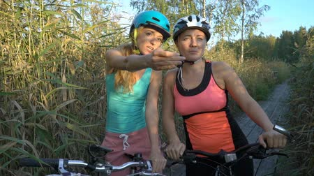 sazlık : Two young women use GPS Navigation At Smartphone On Bicycle while Cycling in nature