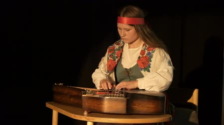 plucked : JYVASKYLA, FINLAND - AUGUST 17, 2018: A young woman in folk costume playing the Kantele - finnish national stringed plucked musical instrument during the international theatre festival Art-Workshop Stock Footage