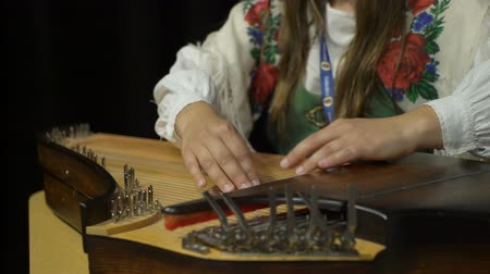plucked : A young woman in folk costume playing the Kantele - finnish national stringed plucked musical instrument. Close up
