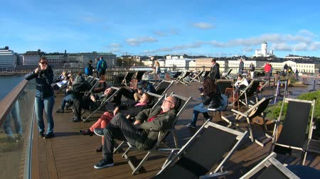 atracação : HELSINKI, FINLAND - NOVEMBER 10, 2018: People enjoy the last Sunny days sitting in the sun loungers on the promenade in autumn in Helsinki