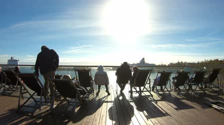 baltské moře : HELSINKI, FINLAND - NOVEMBER 10, 2018: People enjoy the last Sunny days sitting in the sun loungers on the promenade in autumn in Helsinki