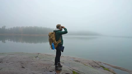 чаща : A middle-aged man walking on a rocky shore of the sea on a misty autumn morning and watching wildlife through binoculars. Slow motion