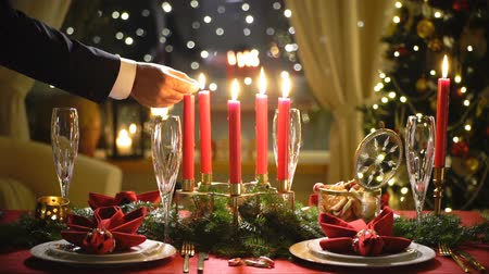 Male hand lights christmas candles. Festival red table setting with garland and Christmas tree in the background Slow motion Stock mozgókép