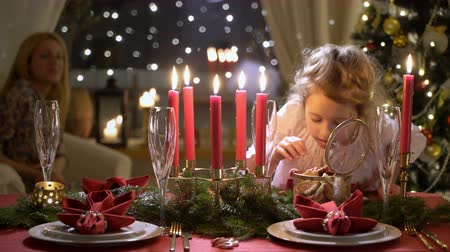 Cute little girl with Christmas cookies. Festival red table setting with candles, garland and Christmas tree in the background Stock mozgókép
