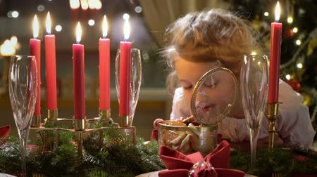 Cute little girl with Christmas cookies. Festival red table setting with candles, garland and Christmas tree in the background Vídeos