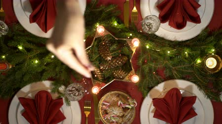 Female hand is pouring confetti on the Christmas table. Festive red table setting with candles and garland. Top view