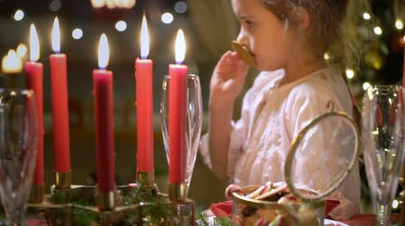 Cute little girl with Christmas cookies. Festival red table setting with candles, garland and Christmas tree in the background. Slow motion
