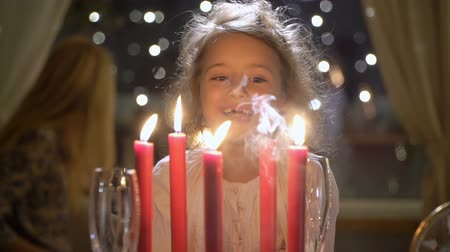 x mas : Cute little girl blowing out red Christmas candles. Slow motion Stock Footage