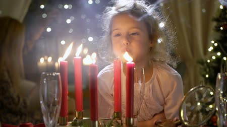 Cute little girl blowing out red Christmas candles. Slow motion Stock mozgókép