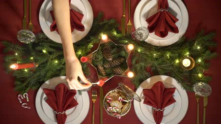 Female hand lights christmas candles. Festive red table setting with garland. Top view. Slow motion