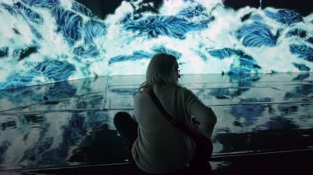 HELSINKI, FINLAND - JAN 06, 2019: Massless Exhibition - immersive interactive graphic digital installations by a group of Japanese artists TeamLab at the Amos Rex Museum. Visitors at museum enjoy the new modern digital art