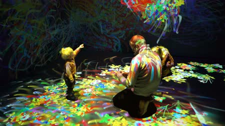 HELSINKI, FINLAND - JAN 06, 2019: Massless Exhibition - immersive interactive graphic digital installations by a group of Japanese artists TeamLab at the Amos Rex Museum. Family with child enjoy the new modern digital art