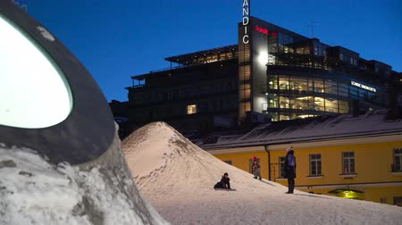 HELSINKI, FINLAND - JAN 12, 2019: Children ride down the snowy Domes of the New Art Museum Amos Rex on the Lasipalatsi Square in Helsinki at night. It is one of Europe's most innovative new architectural space Stock mozgókép
