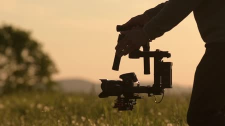 изображение : Video Camera Operator. Videography Theme. DSLR Camera on the Gimbal Stabilization Device. Film Production. Slow Motion Footage