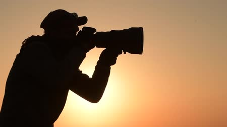 образность : Safari Outdoor Photographer at Sunset. Silhouette of Men Keeping Digital Camera in Hand with Large Telephoto Lens For the Better Wildlife Closeups. Slow Motion Footage