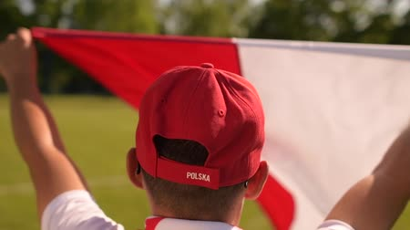 štěrbina : Caucasian Men Wearing Red and White National Colors with Flag Waving on Wind. Slow Motion
