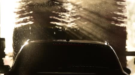 lavagem : Car in the Automatic Car Wash. Spinning Brushes in Slow Motion During Sunset.