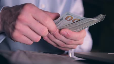 us banknotes : Caucasian Men in His 30s Working Late Hours in the Office. Glassy Desk Closeup Video on His Hands on the Computer Keyboard