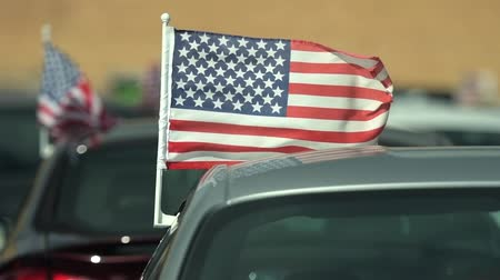 扱う : American Made Cars Sale Concept Photo. Brand New Vehicles For Sale with American Flags Attached. Slow Motion Footage