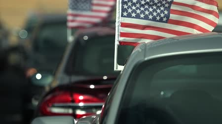 inkoop : Buying American Made Cars. Supporting American Economy Concept Footage with Cars and USA Flag in Slot Motion.