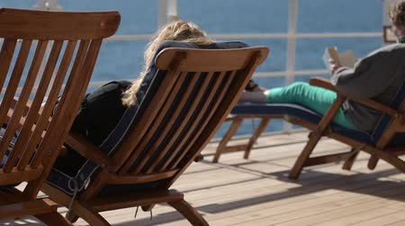 deck chairs : Sea Travel and Cruise Ship Relax. People Relaxing on Deckchairs During Transatlantic Cruise. Slow Motion Footage