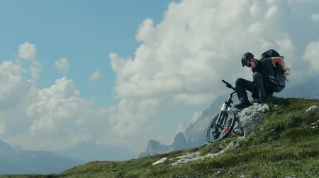 biciclette in montagna : Mountain Biker Riposare e godersi Great Mountain Vista. Alpi italiane Dolomiti.