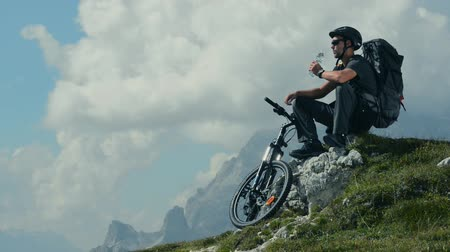 ciclismo : Mountain Biker Drinking Water While Resting on the Mountain Trail