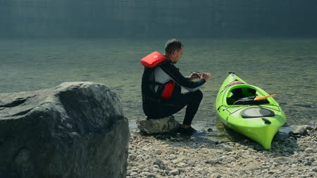 canoa : Kayaker and His Kayak on the Lake Shore Preparing for Another Kayak Trip