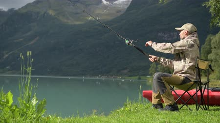 truta : Caucasian Fisherman in His 30s Fly Fishing on the Glacial Lake