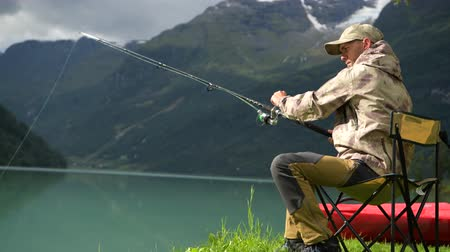 truta : Caucasian Men Fly Fishing on the Scenic Glacial Lake Stock Footage