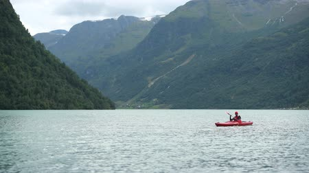 canoa : Kayak Trip on the Lake. Caucasian Men in the Middle of Glacial Lake in Norway.