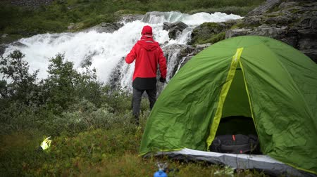 přežití : Caucasian Men Drinking Hot Tea in Front of Waterfall. Camping in the Wild Theme.