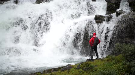 přežití : Exploring the Nature. Caucasian Men in Front of Scenic Norwegian Waterfall