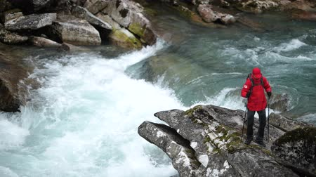 бросаясь : Caucasian Backpacker on the Large River Shore Boulder.