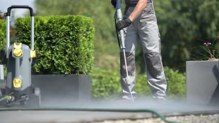 lavagem : Caucasian Worker Cleaning Patio Using Pressure Washer