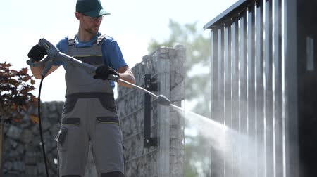 sundurma : Residential Gate Pressure Washer Cleaning. Caucasian Worker in His 30s.