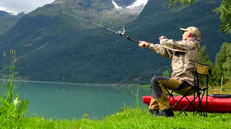 truta : Fisherman in His 30s Fly Fishing on the Scenic Lake. Slow Motion
