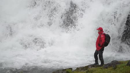 průhled : Caucasian Hiker and the Waterfall Spot. Scenic Norwegian Destination in Slow Motion.