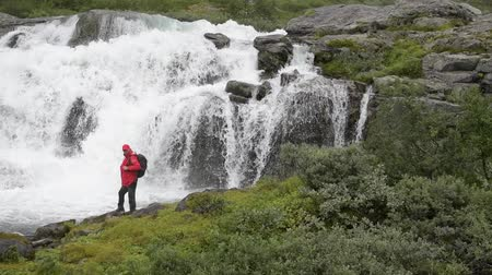 keskeny kilátás : Hiker and the Waterfall Spot. Scenic Norwegian Destination in Slow Motion. Stock mozgókép