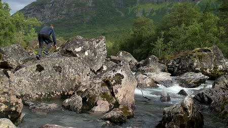 kei : Caucasian Men Enjoying Outdoor Activity. Jumping Between River Boulders. Slow Motion Footage Stockvideo