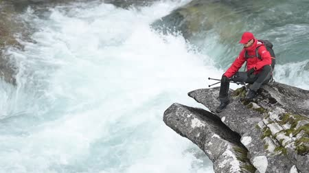 kei : Backpacker with Nordic Walking Poles Relaxing on the River Boulder. Slow Motion Footage Stockvideo