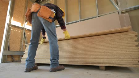 madeira compensada : Worker Moving Plywood Boards. Construction Site. Stock Footage