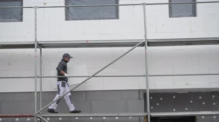 externo : Caucasian Worker on a Scaffolding Working with External Building Insulation. Vídeos