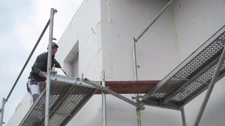 yalıtım : Worker Moving Insulation Blocks on a Scaffolding Stok Video