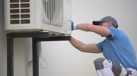 климат : Caucasian Technician in His 30s Installing Brand New Modern Heat Pump