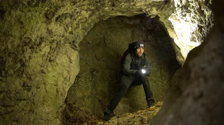 gruta : Rescuer with Flashlight Looking Around in the Deep Cave. Rescue Mission. Stock Footage