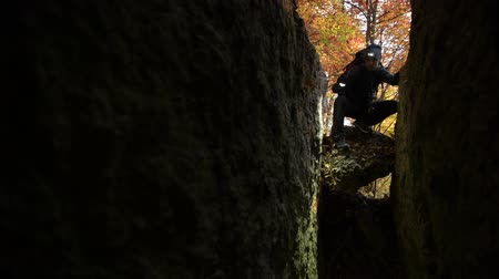 expedice : Hiker with Flashlight Exploring New Cave Entrance. Scenic Fall Foliage in the Background